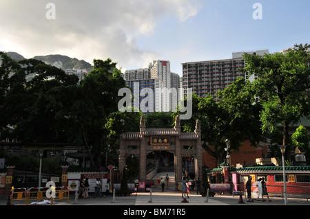 Memorial archway, chinois avec des sculptures sur pierre, l'or nom de temple, des arbres verts et les fidèles, le Banque D'Images