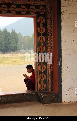 Les jeunes Buddist moine, assis dans une porte ouverte, avec son téléphone mobile. Punakha Dzong, le Bhoutan Banque D'Images