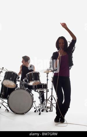 Une chanteuse et un batteur de la scène, Studio shot, fond blanc, éclairage arrière Banque D'Images