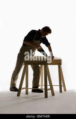 Un menuisier sciant un planche en bois Banque D'Images