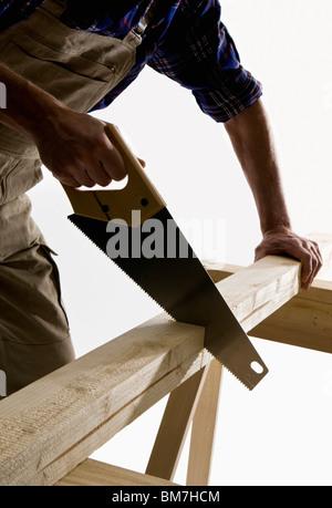 Un menuisier sciant un planche en bois, l'accent sur vu Banque D'Images