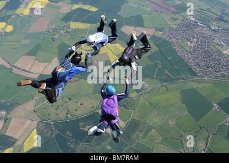Quatre parachutistes en chute libre formations faisant Banque D'Images