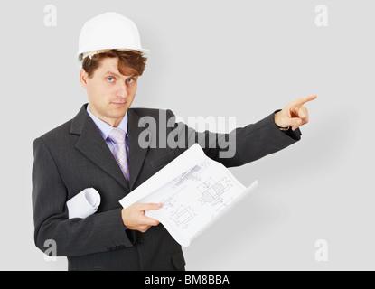 Le jeune ingénieur un bâtiment spécialiste dans un casque avec le dessin dans une main
