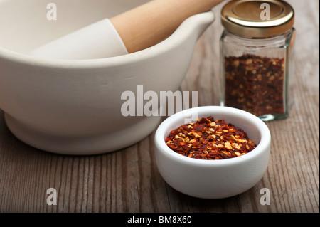 Piments broyés dans un plat blanc, avec un mortier et un pilon et Spice Jar, sur une table de cuisine en bois Banque D'Images