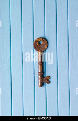Old rusty key squelette bleu sur un fond de bois Banque D'Images