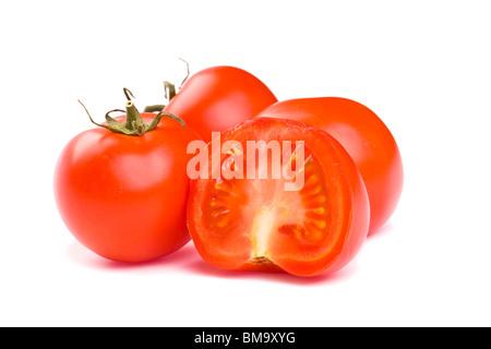 Tomates rouges mûres sur un fond blanc avec chemin de détourage. L'accent est mis sur les tranches de tomate à l'avant. Banque D'Images