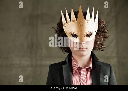 Jeune garçon portant un masque d'or Banque D'Images