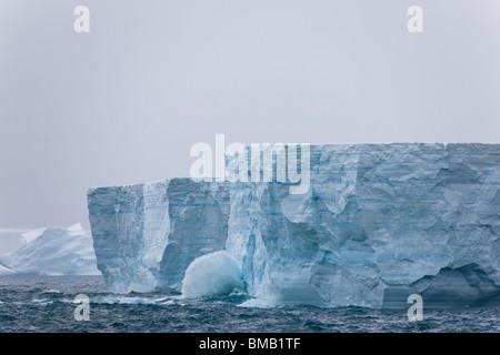 Grand Océan vagues se briser contre de grands icebergs bleu géant d'éroder les énormes icebergs au large de la côte Banque D'Images