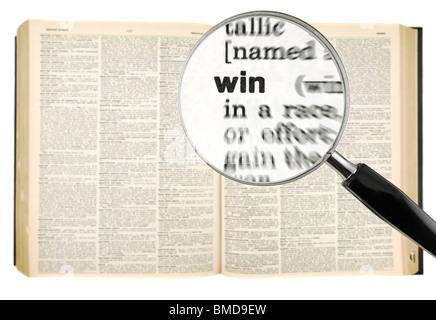Une loupe sur le mot gagner sur un dictionnaire. Isolé sur blanc. Banque D'Images