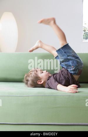 Jeune garçon portant sur canapé vert Banque D'Images