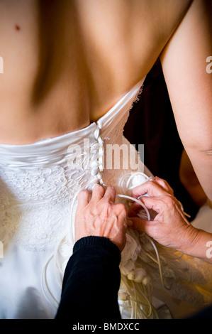 Femme à boutonner la mariée robe de mariage. Banque D'Images