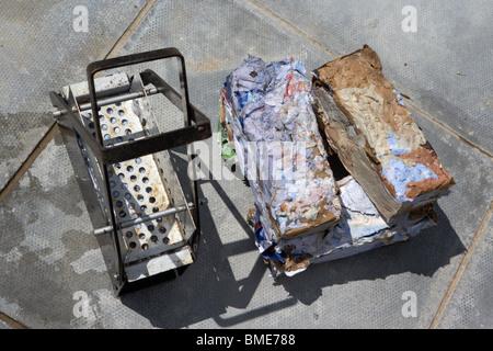 Recyclage des anciens unrecyclable enveloppes et papier dans le briques pour être brûlé dans un incendie au Royaume Banque D'Images