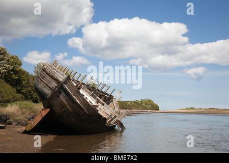 Vieille coque en bois d'une épave sur l'océan à marée de la baie de lagon à Traeth Dulas, Isle of Anglesey (Ynys Banque D'Images