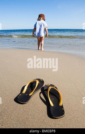 Tongs sur la plage avec la mer en garçon Banque D'Images