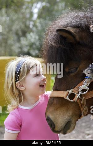 Petite fille blonde adore son pony funny portrait Banque D'Images