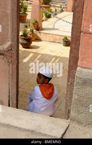 Jeune garçon assis à l'entrée de sa maison dans le sud de la ville du Caire, les cimetières des morts Banque D'Images