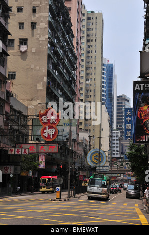 Portrait d'une journée à tablier unique de taxis et bus, à un carrefour, au-dessous de skyscarpers et des enseignes au néon, Lockhart Road, Hong Kong Banque D'Images