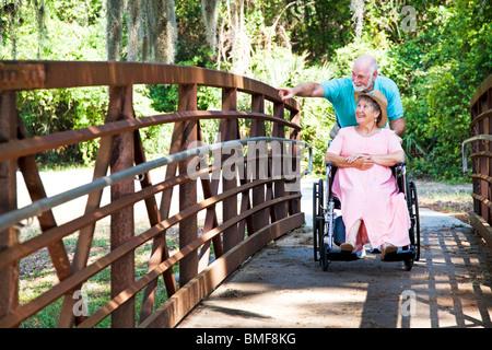Hauts homme pousse sa mobilité femme fauteuil roulant dans le parc. Banque D'Images