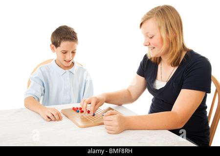 Garçon et fille de jouer à un jeu de dames chinoises. Isolé sur blanc.