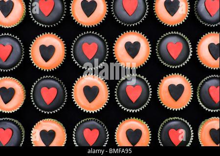 Mini cupcakes décorés de glaçage orange et noir et des formes du coeur Banque D'Images