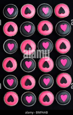Mini cupcakes décorés de glaçage rose et noir et des formes du coeur Banque D'Images