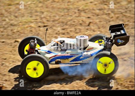 Un modèle de voiture de course de l'accélération de l'avance sur un chemin de terre. Flou sur les roues. Banque D'Images