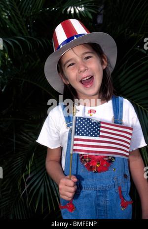 Une magnifique jeune fille dans un chapeau de l'Oncle Sam patriotique vagues le drapeau américain lors d'un 4 juillet Banque D'Images