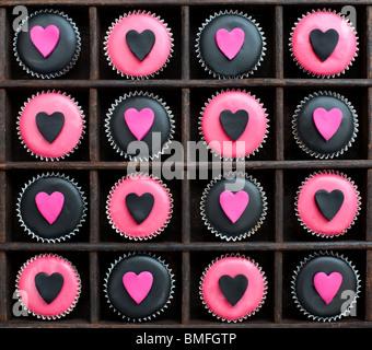 Mini cupcakes décorés de glaçage rose et noir et le coeur des formes dans un plateau en bois Banque D'Images