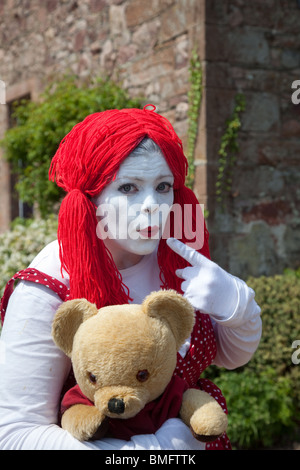Women's Clown poupée de chiffon robe de soirée. Un effrayant femme vêtue avec perruque rouge, peint en blanc, face Banque D'Images