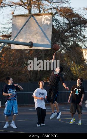 Oriental de jeunes adolescents jouant au basket-ball dans l'après-midi, Auckland, Nouvelle-Zélande