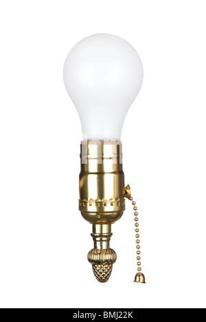 Une ampoule dans une douille en laiton avec chaîne de traction. Banque D'Images