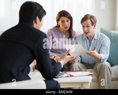 Planificateur financier talking to couple dans leur maison Banque D'Images