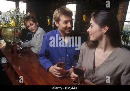 Un couple ayant un verre ensemble dans un bar avec une femme dans l'arrière-plan à la marre Banque D'Images