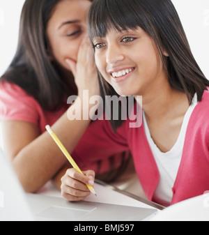 Les élèves en classe whispering Banque D'Images