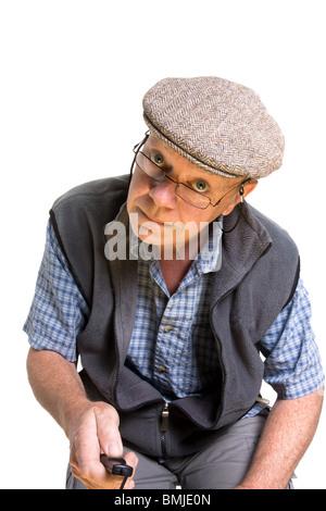 Vieil homme expressif de l'interrupteur à distance d'exploitation isolés contre fond blanc.