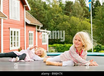 Deux soeurs gisant sur rebouncer Banque D'Images