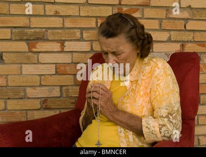 Femme priant son chapelet Banque D'Images