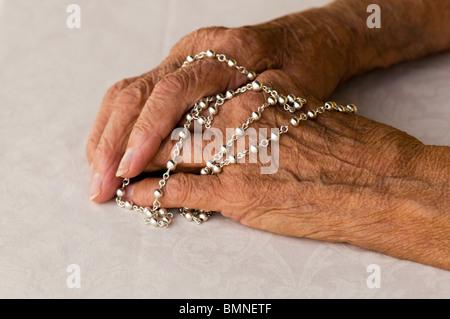 De gros plan femme priant son chapelet Banque D'Images