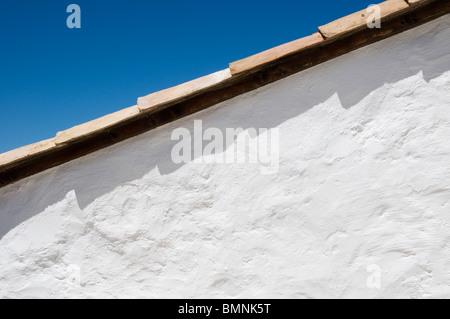 Mur blanchi à la chaux et un toit de tuiles contre un ciel bleu Banque D'Images