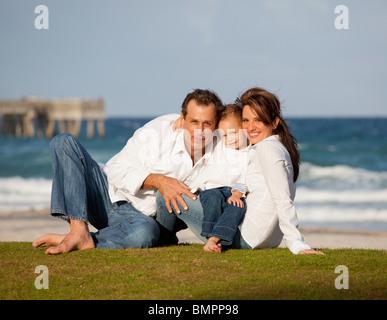 Fort Lauderdale, Floride, États-Unis d'Amérique; une famille assis sur l'herbe par l'Océan Banque D'Images
