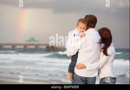 Fort Lauderdale, Floride, États-Unis d'Amérique; une famille sur la plage en regardant un arc-en-ciel dans le ciel Banque D'Images