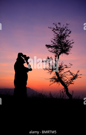 L'homme de prendre en photo le coucher du soleil; Village; District Talegaon Pune Maharashtra; Inde; Banque D'Images
