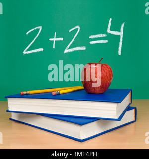 2 + 2 = 4 écrit sur un tableau. Des livres, des crayons et une pomme sur l'avant-plan. Banque D'Images