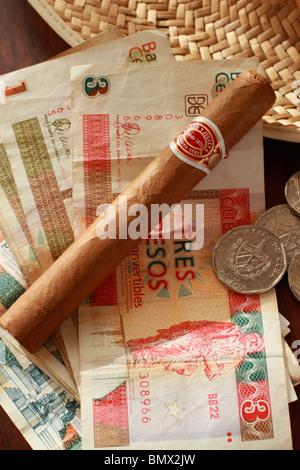 Un cigare cubain Romeo & Julieta sur fond de billets et pièces cubaines Banque D'Images