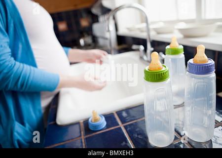 Femme enceinte lave-biberons Banque D'Images