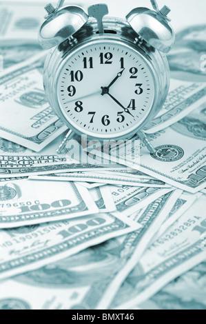 - Le temps de l'argent. Concept d'entreprise. Heures analogique sur un tas de papier de dollars. Ton bleu Banque D'Images