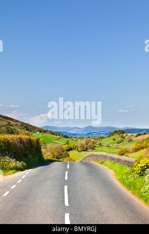 Route panoramique ouvert à travers la campagne anglaise vers les montagnes du Lake District on a road trip en Cumbria Banque D'Images