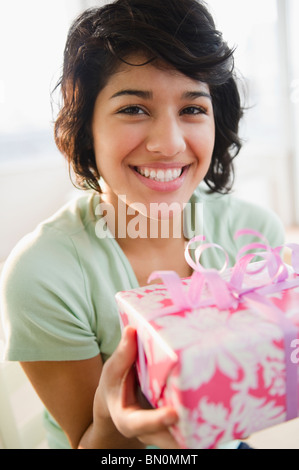 Hispanic woman holding birthday gift Banque D'Images