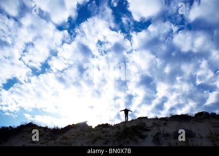 Jeune mec sur dunes en silhouette Banque D'Images