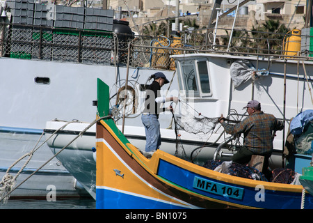 Un père et sa fille préparent leurs filets de pêche sur un bateau de pêche traditionnel maltais de couleur. Marsaxlokk, Banque D'Images